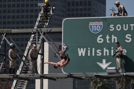 Nearly naked man who scaled Los Angeles freeway sign causes traffic jam