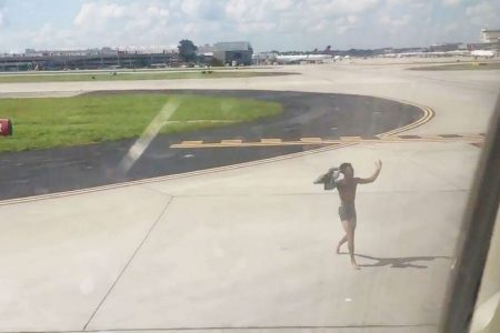 Man jumps onto wing of plane on active taxiway after scaling fence at Atlanta airport, police say