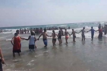 Beachgoers battle deadly rip currents by forming human chains