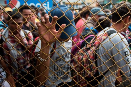 Thousands in a migrant caravan wait to cross the Guatemalan-Mexican border amid sweltering heat